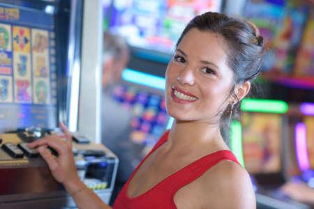 beautiful woman in red dress playing slot machine