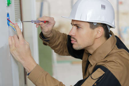 young electrician installing electrical socket on wall with screwdriver