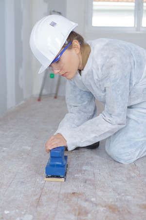 handywoman sanding wooden floor in construction site
