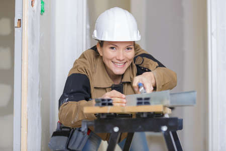 female builder polishing the plank