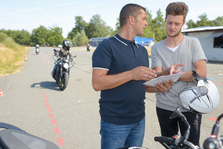 motorbike instructor showing a paper to the student Stock Photo