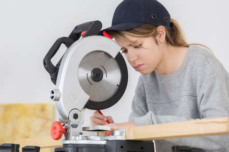 young female carpenter using a circular saw to cut