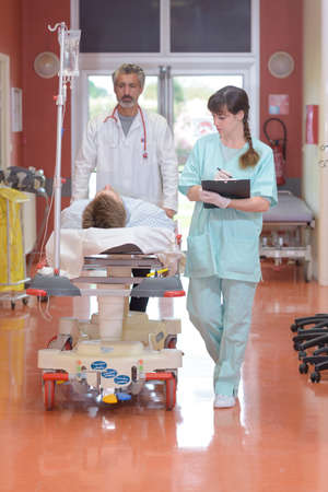 doctors carrying a patient on hospital gurney Stock Photo