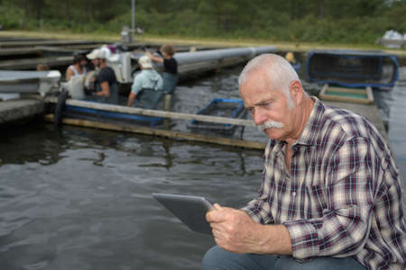 experienced fish farm manager holding tablet