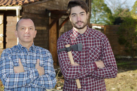 two friends lumberjacks in the forest with an axe