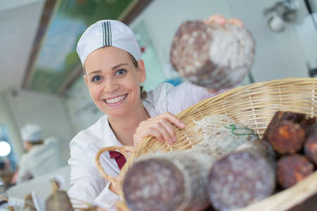 portrait of female seller offering wursts in local butchery Stock Photo