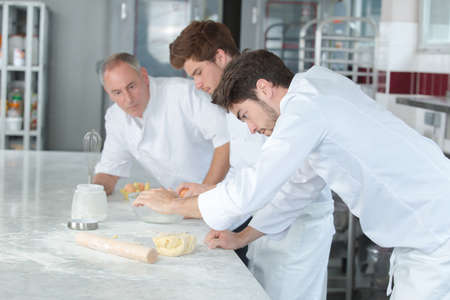 concentrated male pastry with apprentices