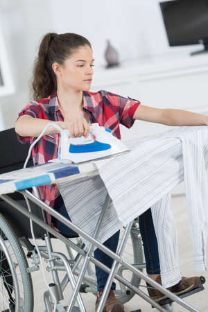 young disabled woman is ironing at home Reklamní fotografie