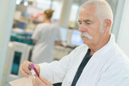 senior male scientist examining blood test tubes at his laboratory