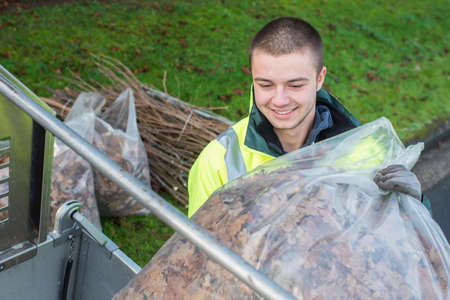 young worker loading bag of dead leaves into vehicle Stock Photo