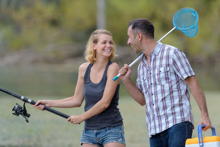 happy excited man and woman fishing on the pond