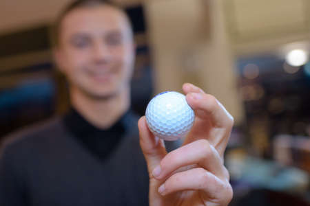 hand of a man holding a golf ball Stock Photo