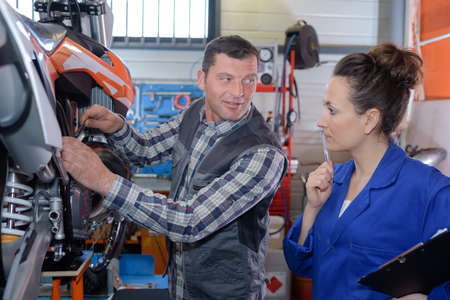 woman mechanic repairing a motorcycle in a workshop with coleague