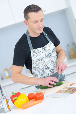 man chopping vegetables in kitchen Stock Photo