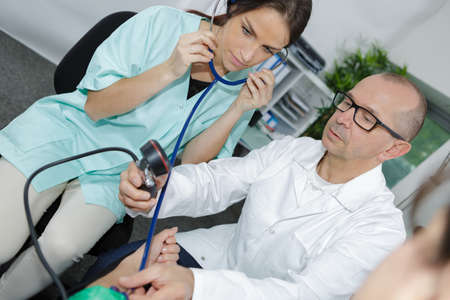 experienced doctor with pretty internist during blood pressure test