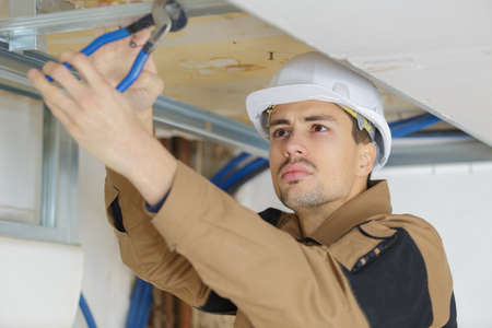 handsome young man fixing ceiling panel with pliers