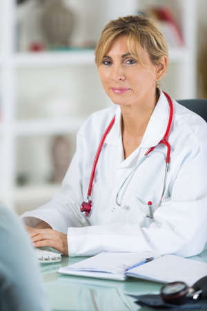 pensive female doctor at her desk Stock Photo