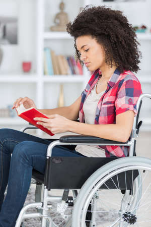 woman on the wheelchair reading a book
