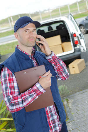 delivery man holiding clipboard and talking on telephone 스톡 콘텐츠