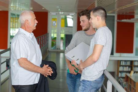 professor talking to students in corridor