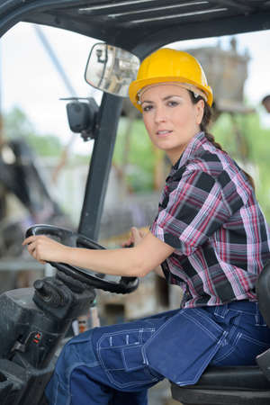 female fork lift truck driver in factory