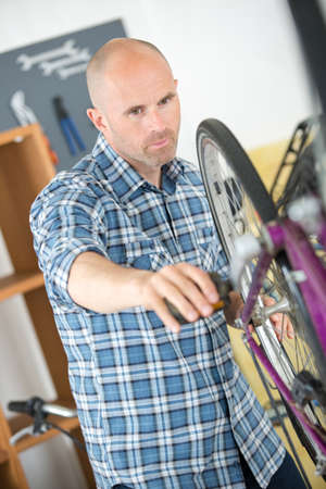 young man repairs a bicycle Foto de archivo
