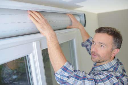 man installing cassette roller blinds on windows Stock fotó