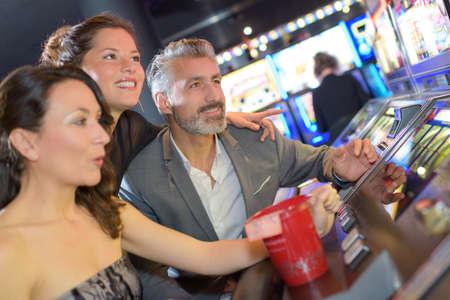 three adults sat excitedly around casino machine Stock Photo