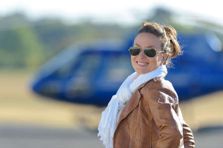 pretty pilot woman on helicopter background vintage filtered image