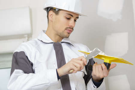 young man plasterer working on wall in building construction Stock Photo