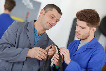 apprentice inspecting a rubber belt with the teacher
