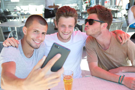 Three young men taking selfie with smartphone