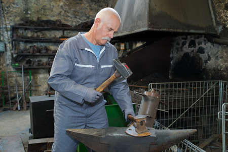 Metalworker at anvil, holding hammer