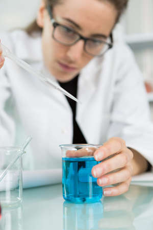 female trainee working with chemical liquids in lab