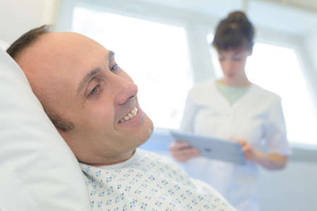 happy patient lying on hospital bed