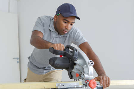 carpenter using circular saw for wood