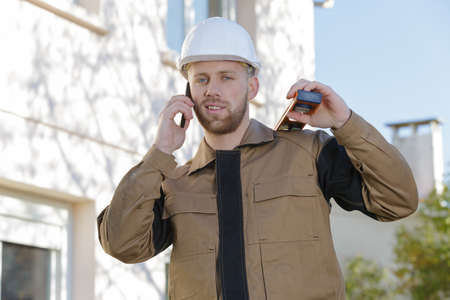 portrait of contractor outdoors using telephone spirit level on shoulder Stockfoto