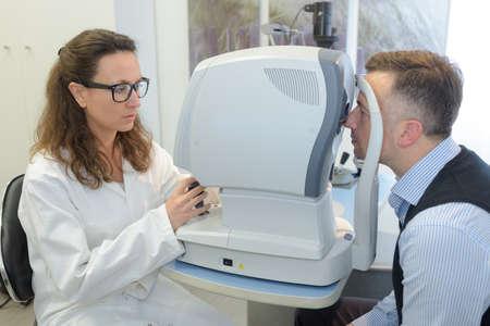 ophthalmologist examining mans eyes