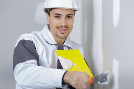 male plasterer in uniform polishing the wall Stock Photo