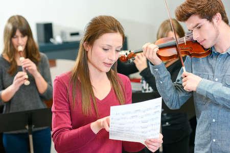 music teacher tutoring young man to play violin Stock Photo