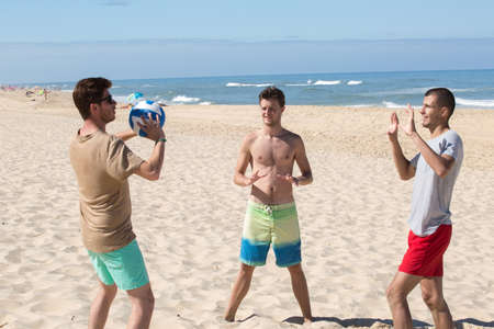three young men having fun on the beach playing volleyball