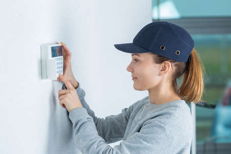 young female technician installing security system