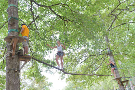 happy people climbing on the ropes in adventure park Stock Photo