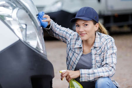 Woman cleaning front of van