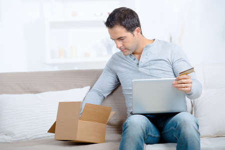 man with credit card and computer laptop with box purchases