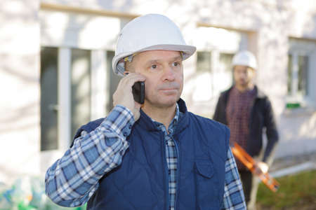 construction engineer talking by phone on building site