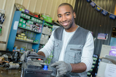 male mechanic with used vehicle battery on shop counter Stock Photo