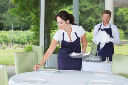 2 waiters setting the table in a fancy restaurant Stock Photo