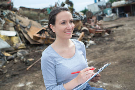 woman in the junkyard holding clipboard Stock Photo