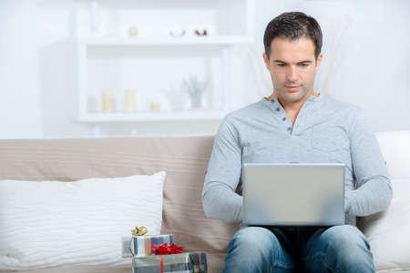 Man on internet, gifts beside him